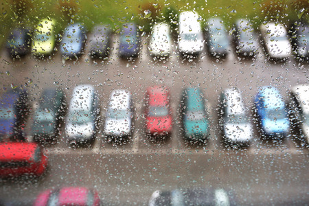 A glass with raindrops and a top view of parking car on a blurred background.