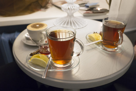 A transparent glass mug of black tea and a lemon close-up on a white round table in a cafe.