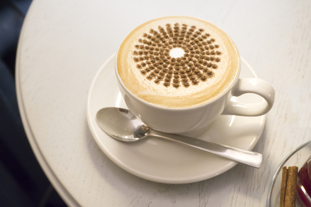 A cappuccino cup decorated with cinnamon on a white round table. Close up.