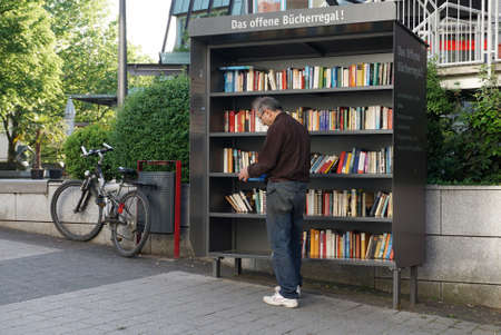 Backnang, Baden-Wurttemberg, Germany - May 9, 2018: A man standing by a street rack with free books.