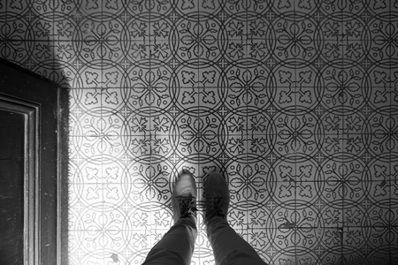 A look down at the feet and floor decorated with vintage patterned tiles. Black white composition.