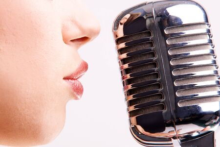 shure: pop female singer with the retro microphone  Stock Photo