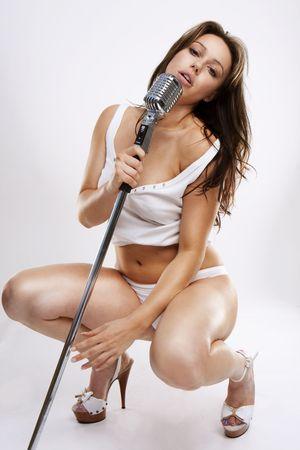 rocker girl: glamour sexy cantante estrella del pop con ropa blanca y retro micr�fono Foto de archivo