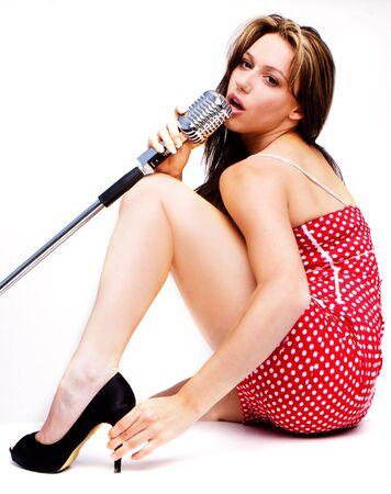 sexy kobiety w czerwonej sukni postrzelony z mikrofonem