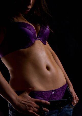 navel piercing: sporty looking woman posing in lingerie Stock Photo