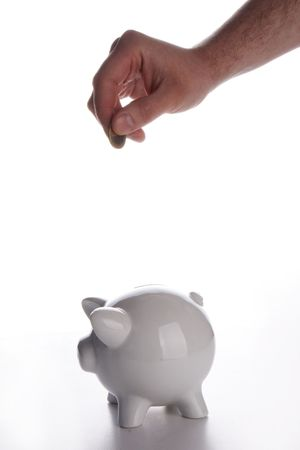male hand dropping a coin of one euro into a white piggy bank. photo