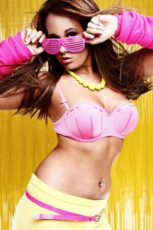 night clubs: sexy female dancer waring pink bra and funky shutter shades glasses on yellow background