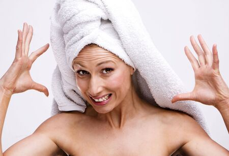 Young sexy emotional gorgeous female in wrapped in bathtowel and screaming photo