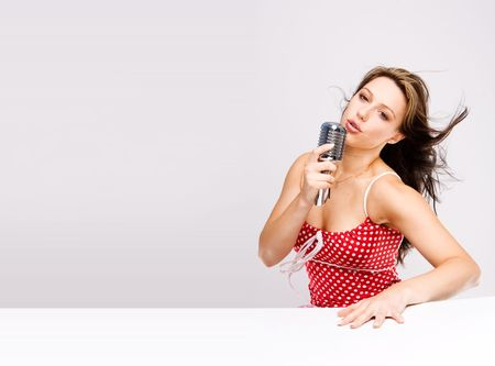 sexy women in dotty red dress with microphone on isolated background photo