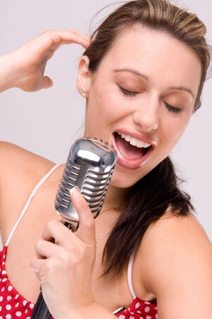 sexy women in dotty red dress with microphone close-up photo