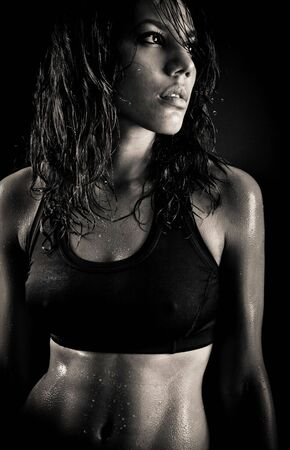 portrait of sexy fitness wet woman on isolated black background Stock Photo