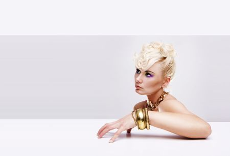 fine gold: pretty blonde model with gold charm bracelet retro hairstyle and color makeup Stock Photo