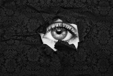 Female eye peeking through a hole in black wallpaper photo