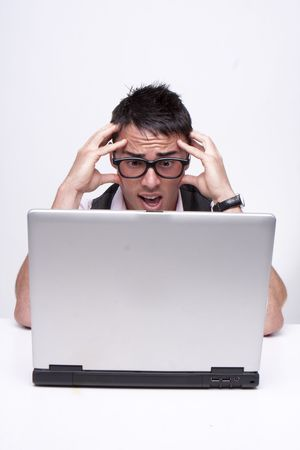 Brunette businessman looks at his computer in disbelief isolated on white  photo