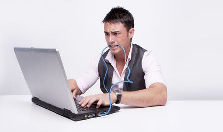 Brunette businessman looks at his computer in disbelief beating network cable  photo