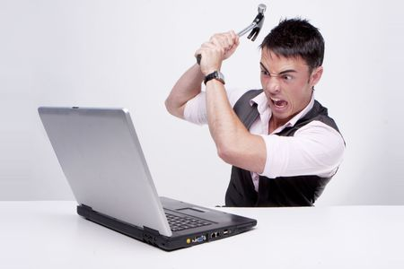 Brunette businessman looks at his computer in disbelief killing his computer using a hammer