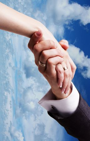 Close-up of bride hand holding that of her husband over sky background  photo