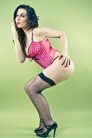 pin-up picture of sexy lady in pink corset on green background Stock Photo - 5220403