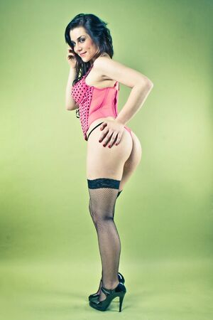 pin-up picture of sexy lady in pink corset on green background photo