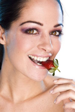 Beautiful young woman face. Close up. Portrait of young girl witn fresh strawberry photo
