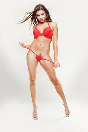 sexy breasts: Studio fashion portrait of a beautiful young woman with long dark hair in red bikini, isolated