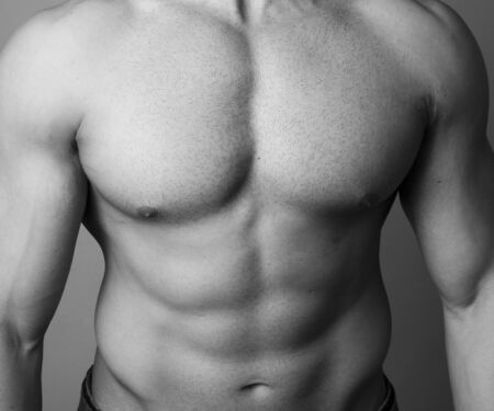 washboard: Abs of a muscular man on grey background