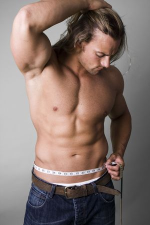 muscular body: Muscular man measuring his waist