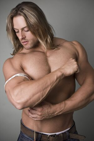 pectorals: A bodybuilder measuring the increase in his bicep