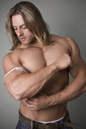 A Bodybuilder pomiaru wzrostu jego Bicep Zdjęcie Seryjne
