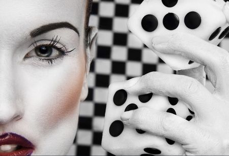face covered: Abstract of a closeup of a portion of a womans face in white makeup, her white painted hand beside her head holding a large set of dice. Set against a black and white checkered background.