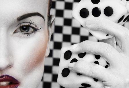 Streszczenie Zbliżenie część kobiecej twarzy w białym makijażu, białe malowane ręcznie obok głowy gospodarstwa duży zestaw kości. Na tle czarno-białym tle kratkę. Zdjęcie Seryjne
