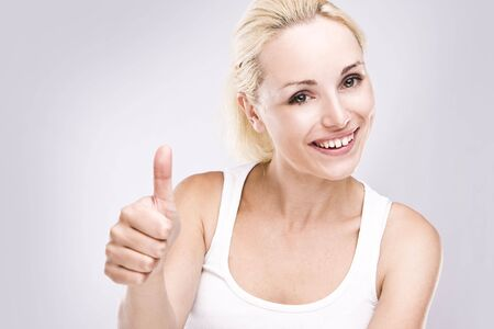 Portrait of an attractive young female with thumbs up. Stock Photo - 5292562