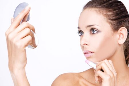 Makeup - Beautiful woman applying lipstick holding small mirror Stock Photo - 5313803