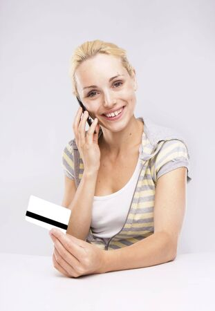 Blond Woman Credit Card Shopping via phone isolated  photo