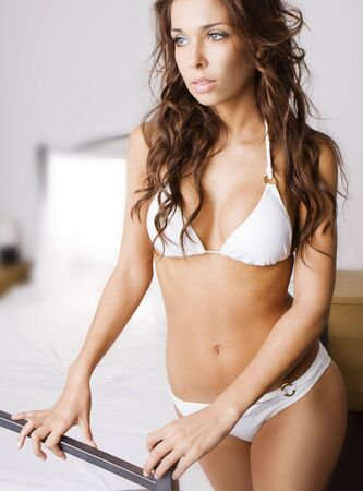 Young brunette woman on the bed Stock Photo - 5333015
