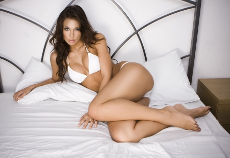 Young brunette sexy glamour woman in white bikini on the bed