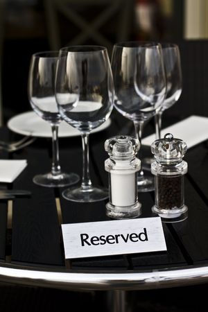 reserved table in the restaurant of bar  with the wine glasses , salt and pepper  photo