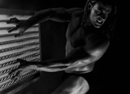sculpted:  Dramatic image of a beautifully sculpted bodybuilder in the cage