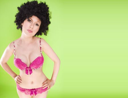 beautiful woman in a big afro wearing pink lingerie on green background photo