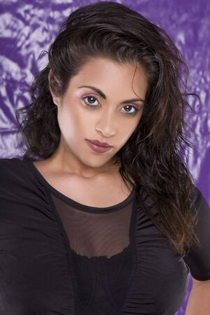 flicking:  young attractive Indian model  on violet background