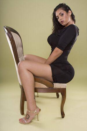 culo: modelo de India de glamour sexy sentado en la silla con estilo en el estudio