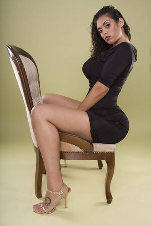 flicking: sexy glamour indian model sitting on stylish chair in the studio Stock Photo