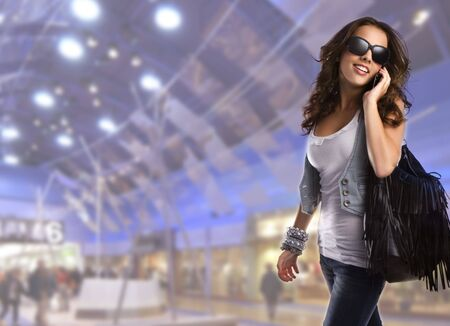 mobile shopping: Young teenage woman wearing sunglasses walking in the shopping centre