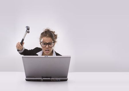 Angry brunette businesswoman with hammer and glasses against laptop photo