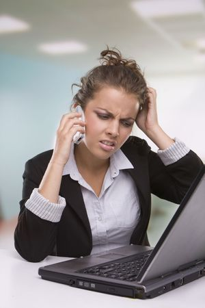 Portrait of tired secretary working in office speaking over the phone and using laptop Stock Photo - 5579574