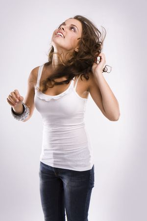 undressing woman: isolated nice woman on jeans and white tanktop dancing  Stock Photo