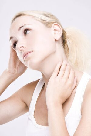 close up of a blonde woman massaging her neck on grey background photo