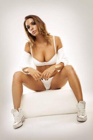 erotico: Sexy donna giovane indossava lingerie bianca, camicia e scarpe sportive in studio