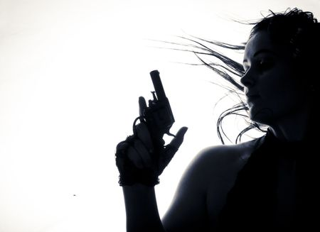 Beautiful young women with gun. Isolated. low-key  photo