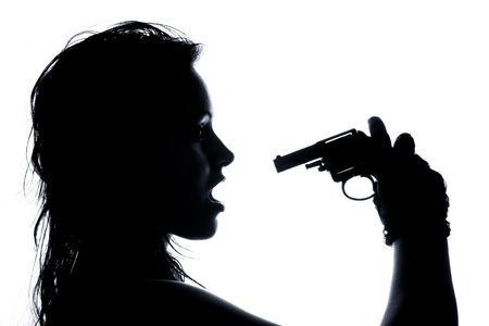 close-up portrait of beautiful girl pointing pistol at her open mouth  photo